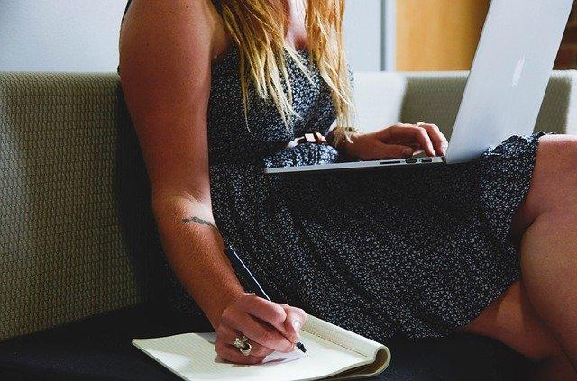 Empleada trabajando con portátil y bloc de notas
