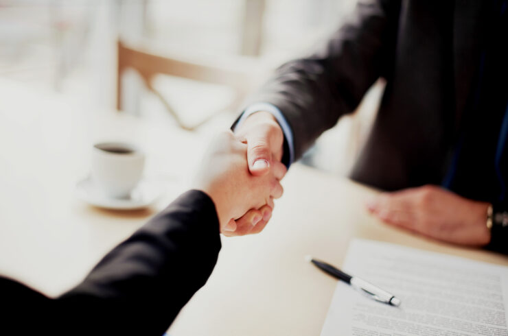 Close-up of two individuals wearing suits and shaking hands while seated at a desk across from one another.