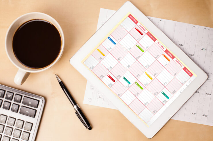 Overhead view of a desk covered with a keyword, mug of coffee, a pen, a paper calendar, and a smart tablet displaying a work schedule.