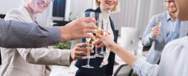 A group of individuals in office apparel gather in a circle, toasting glasses of champagne in celebration.