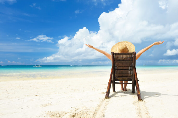 A person sitting on a wooden chair while wearing a straw sun hat on a white sand beach, clouds in the bright blue sky and the ocean visible on the horizon.