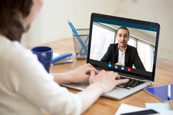 Over-the-shoulder view of an individual seated at a desk with a mug of coffee, chatting on a laptop via video call with another individual.