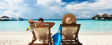 Two people are relaxing in beach chairs on a beach. They are looking out at the sea, clouds, and small vacation homes.